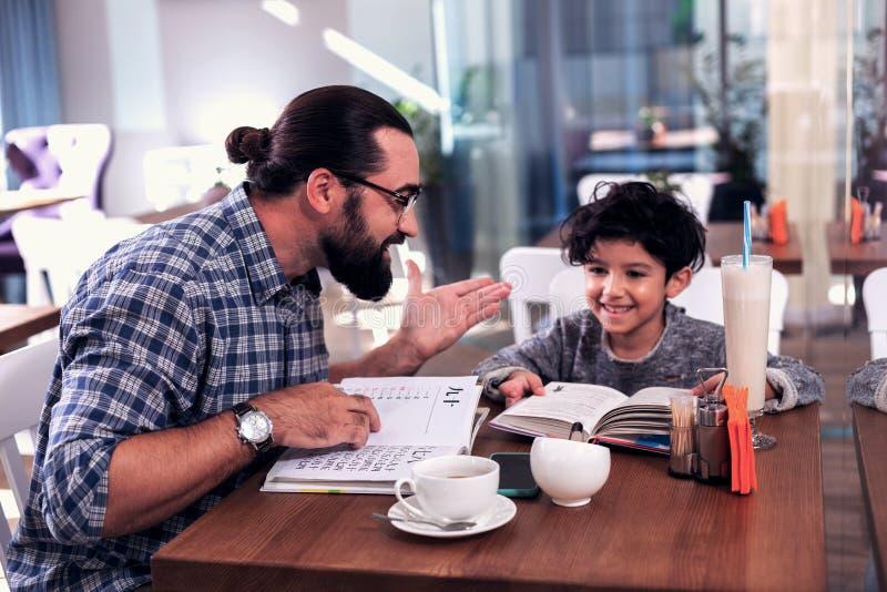 有深色头发的外国语的家庭教师与逗人喜爱的学龄前儿童的类 库存图片