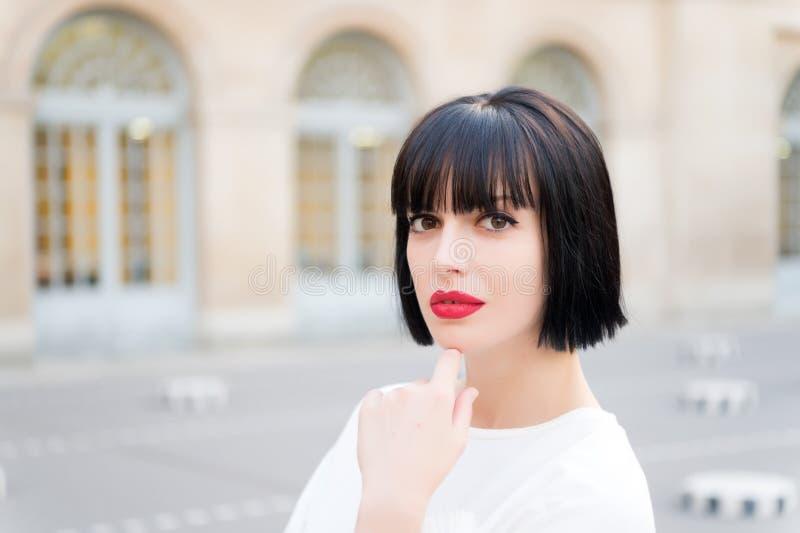 有深色的头发和红色嘴唇构成面孔的妇女在巴黎, 免版税库存图片