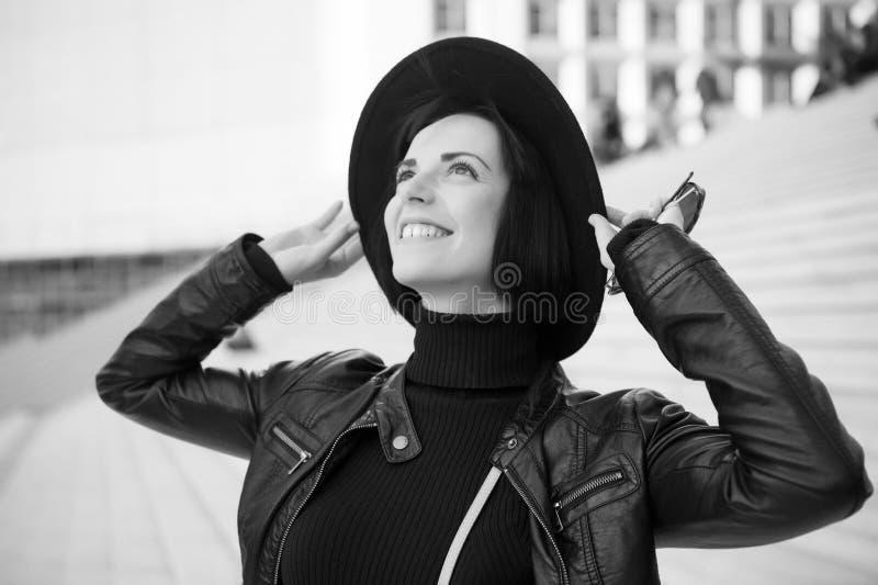 有深色的头发微笑的妇女在黑帽会议 库存图片