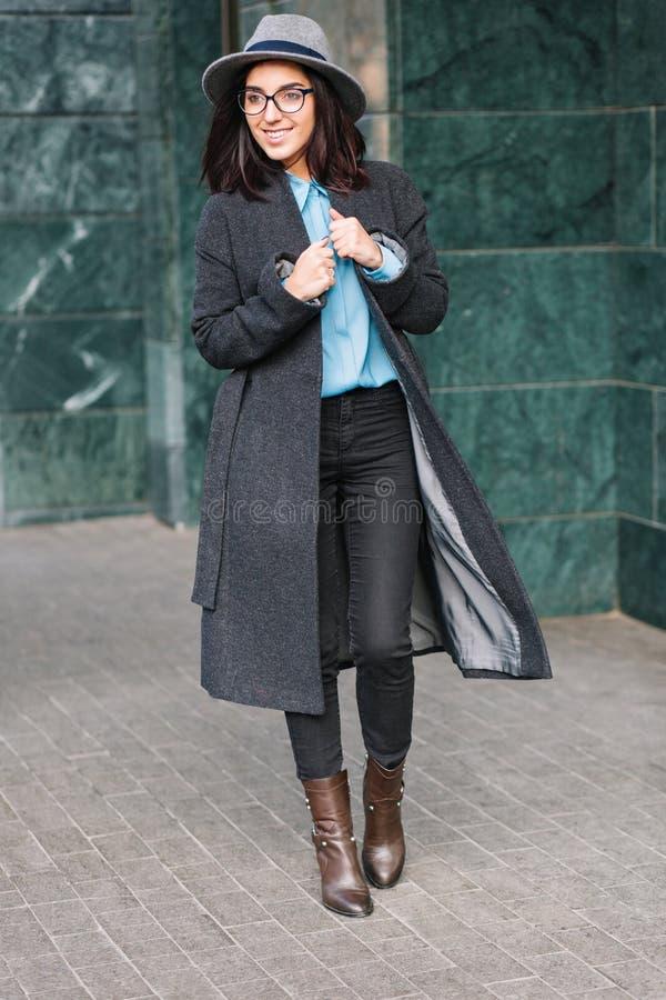 有深色的头发的快乐的微笑的年轻女人在长的灰色外套走在街道上的在城市 黑玻璃,帽子,蓝色衬衣 免版税库存图片