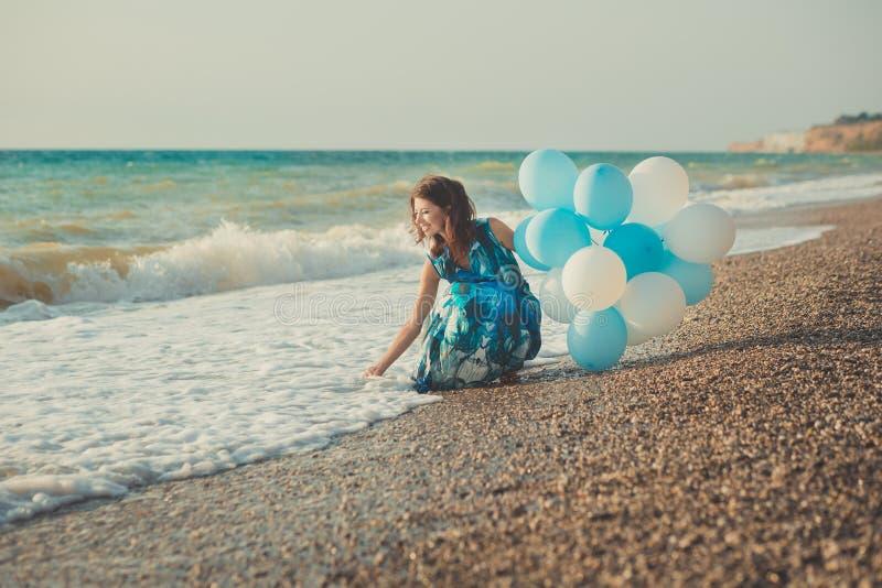 有深色的头发的惊人的肉欲的夫人妇女和与白色气球摆在的冰蓝色眼睛为照相机坐夏天沙滩w 库存照片