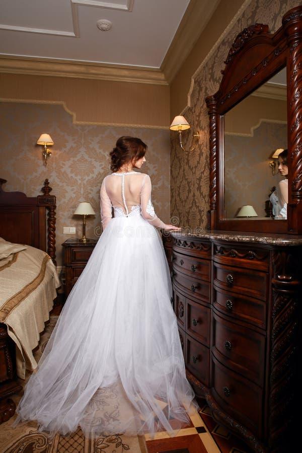 有深色的头发的美丽的年轻新娘在卧室 经典白色婚礼礼服 全长纵向 库存图片