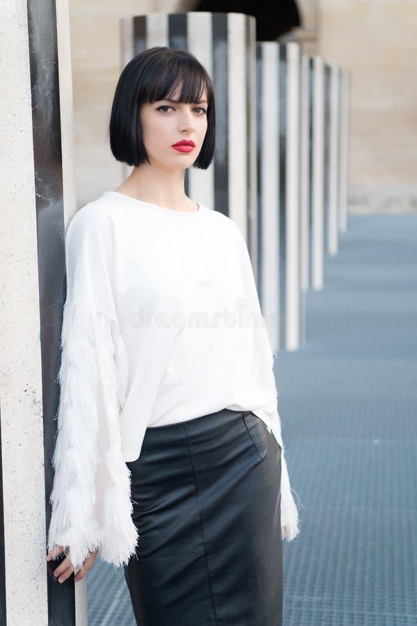 有深色的头发的肉欲的妇女 有红色嘴唇构成的妇女在巴黎,法国 有魅力神色的秀丽女孩 在whi的时装模特儿 免版税库存图片