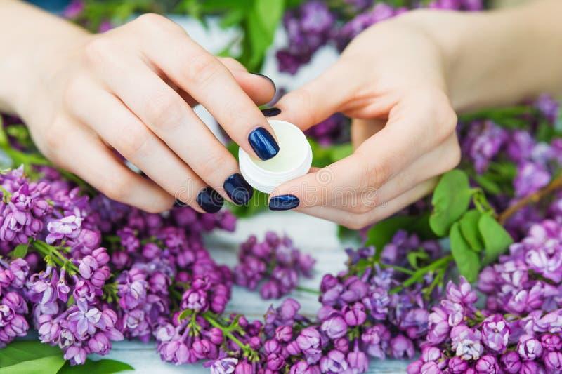 有深蓝修指甲和丁香花的妇女手 免版税图库摄影