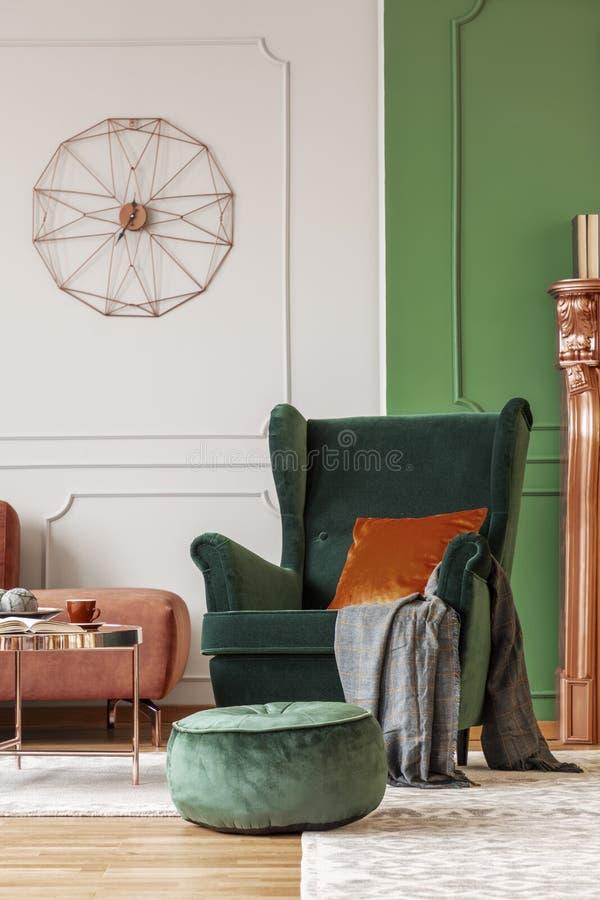 有深黄枕头的典雅的绿色扶手椅子 免版税库存照片