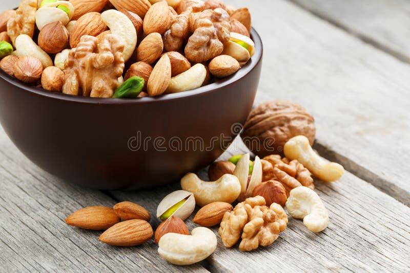 有混杂的坚果的木碗在木灰色背景 核桃、开心果、杏仁、榛子和腰果,核桃 免版税图库摄影