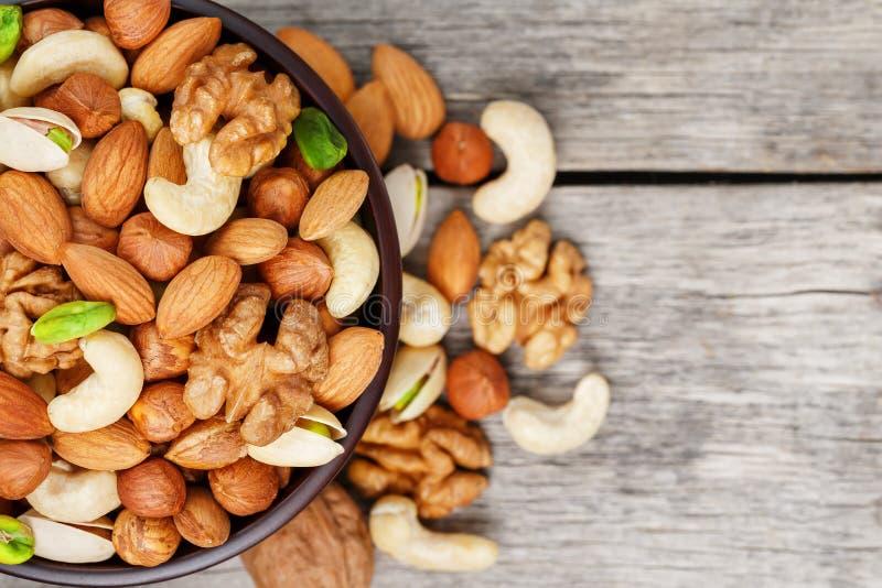 有混杂的坚果的木碗在木灰色背景 核桃、开心果、杏仁、榛子和腰果,核桃 免版税库存图片