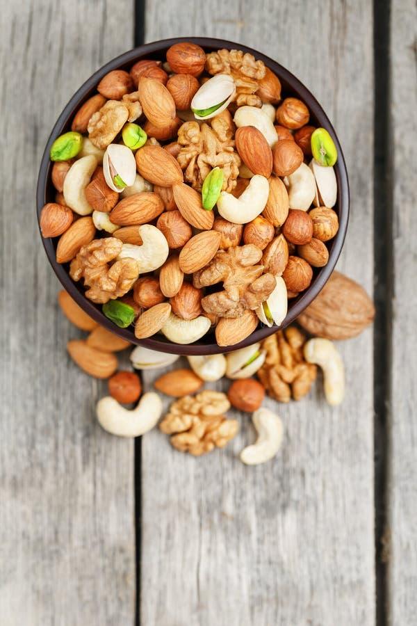 有混杂的坚果的木碗在木灰色背景 核桃、开心果、杏仁、榛子和腰果,核桃 库存照片