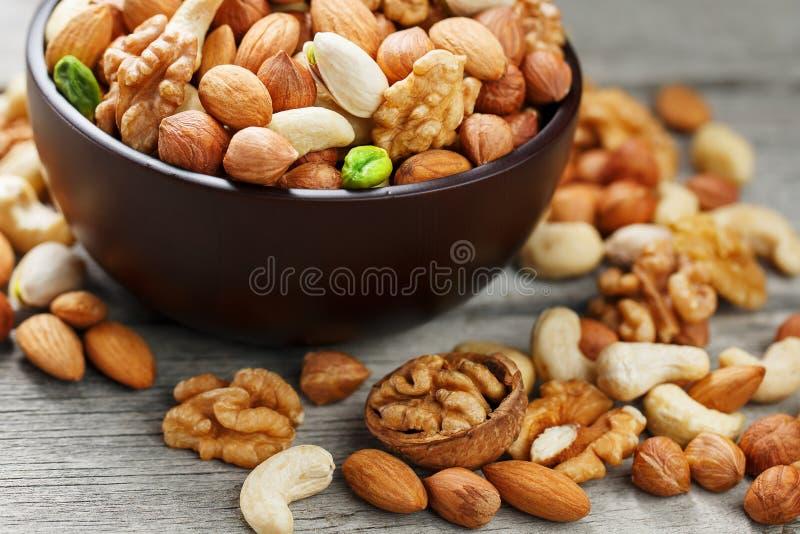 有混杂的坚果的木碗在木灰色背景 核桃、开心果、杏仁、榛子和腰果,核桃 库存图片