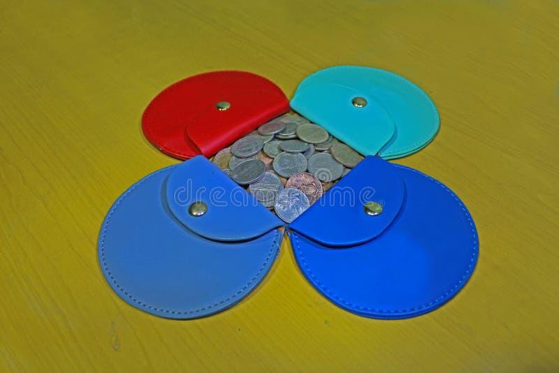 有混杂的硬币的五颜六色的钱包 库存图片