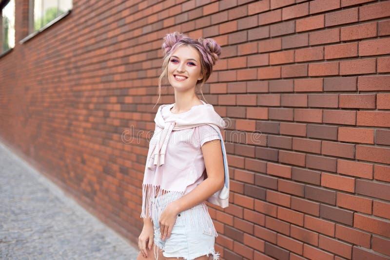 有清楚的皮肤、明亮的桃红色构成和白色牙的美丽的微笑的妇女用在红砖背景的头发小圆面包 图库摄影