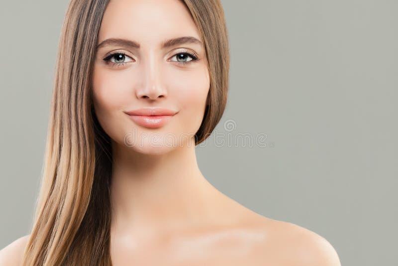 有清楚的皮肤和长的平直的棕色头发的俏丽的妇女 脸蛋漂亮特写镜头 免版税库存照片