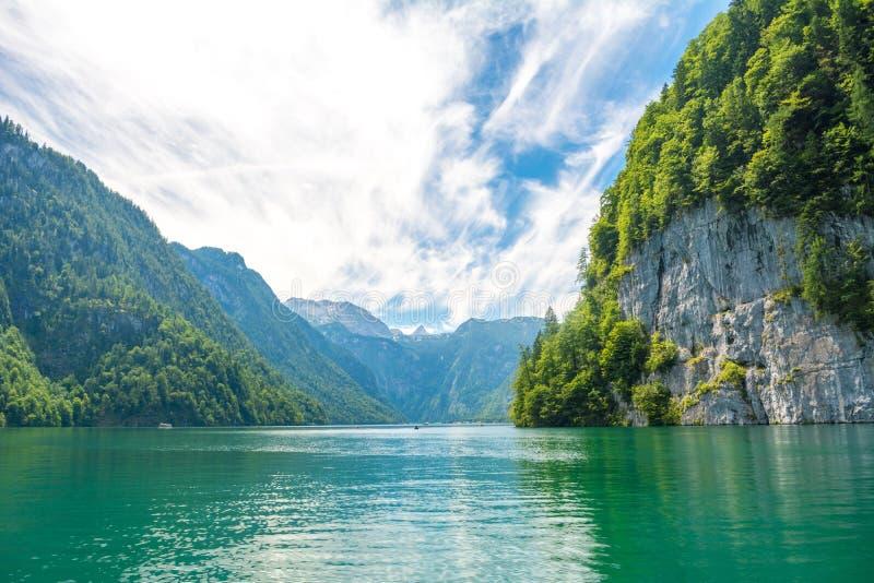 有清楚的绿色水、反射、山和天空背景的,巴伐利亚,德国Konigssee湖 免版税库存图片
