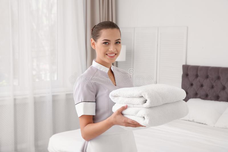 有清洁毛巾的年轻女服务生 免版税库存照片