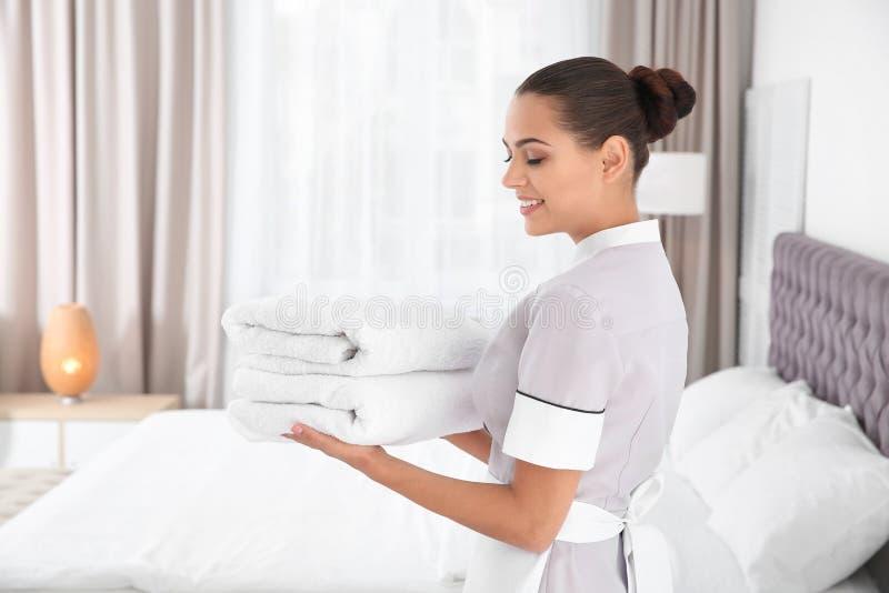 有清洁毛巾的年轻女服务生 库存照片
