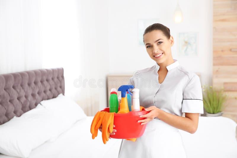 有清洁物品的年轻女服务生在卧室 免版税库存照片