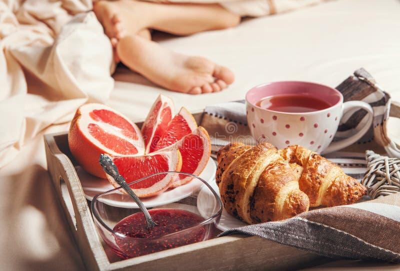 有清淡的早餐的盘子在床上 免版税库存照片
