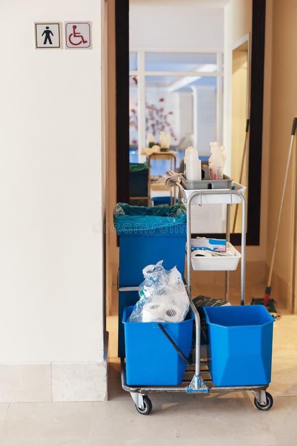 有清洁物品的,在洗手间附近的擦净剂推车 免版税图库摄影