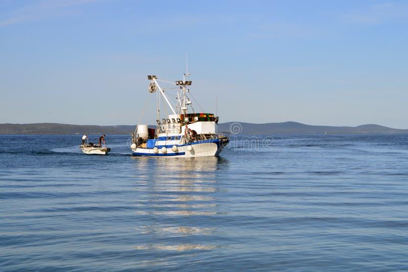 有渔夫的渔船在镇静蓝色海 库存图片