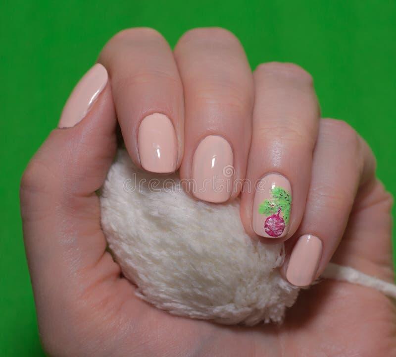 有温文地横渡她的手的美丽的被修剪的桃红色指甲盖的妇女显示他们到在a的观察者圣诞树 免版税库存图片