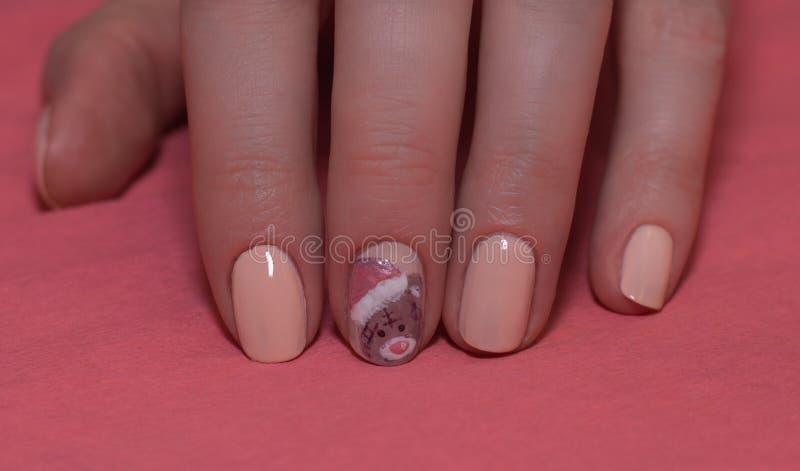 有温文地横渡她的手的美丽的被修剪的桃红色指甲盖的妇女显示他们到在a的观察者圣诞树 库存照片