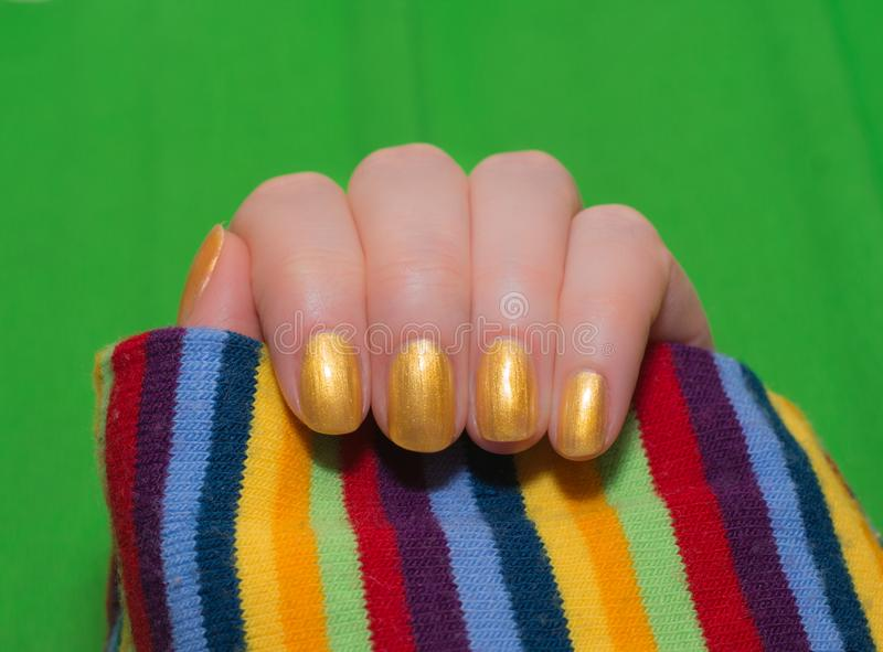 有温文地横渡她的手的美丽的被修剪的金指甲盖的妇女显示他们到观察者raindow时尚, 免版税库存照片