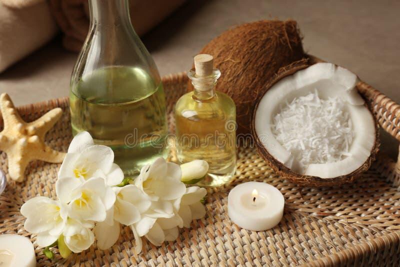 有温泉油、椰子、蜡烛和花的盘子 免版税图库摄影