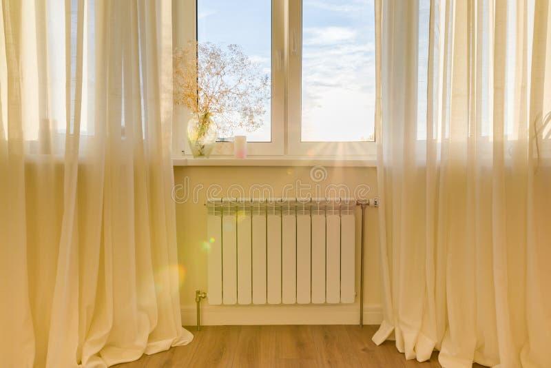 有温箱的白色幅射器在公寓 在窗口下的加热器 免版税库存照片