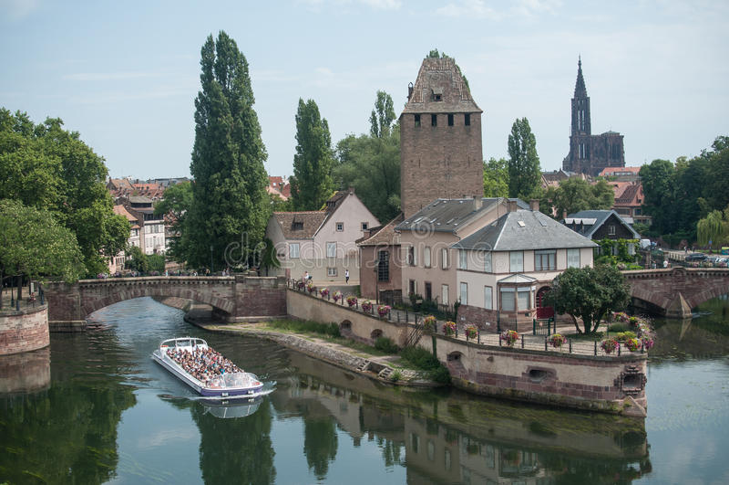 有游人的小船在一点法国处所的中世纪塔的在史特拉斯堡 库存照片