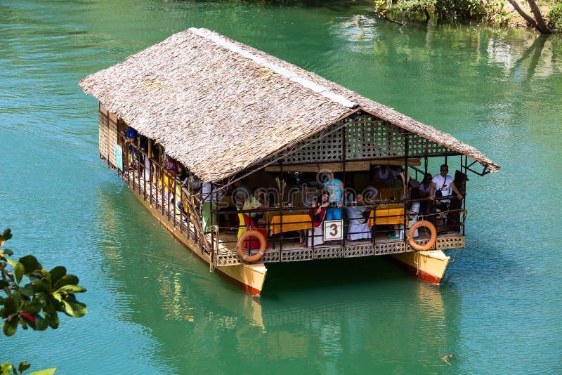 有游人的异乎寻常的巡航小船密林河的 海岛保和省,菲律宾 库存照片