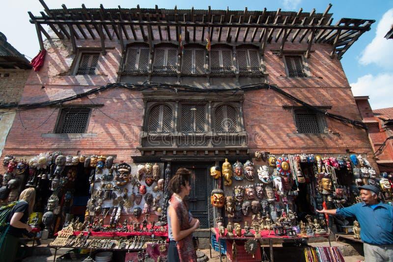 有游人的猴子寺庙的,加德满都市,N一家面具商店 免版税库存照片