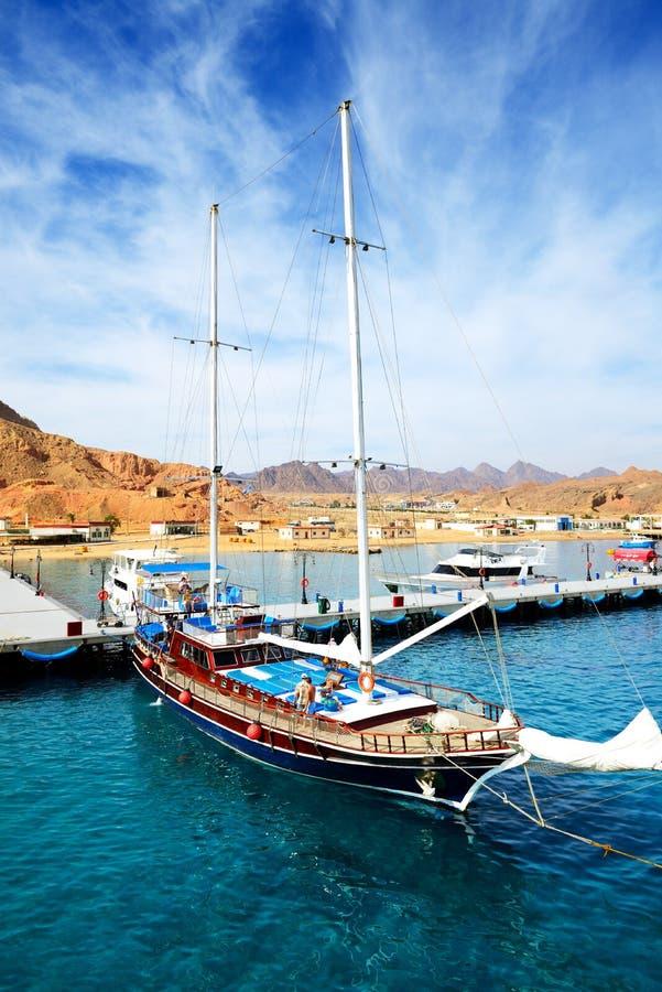 有游人的风帆游艇是近的码头在Sharm El谢赫港口  免版税库存图片