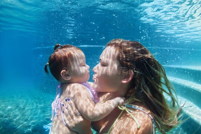 有游泳在水面下在蓝色海滩水池的孩子的母亲 图库摄影