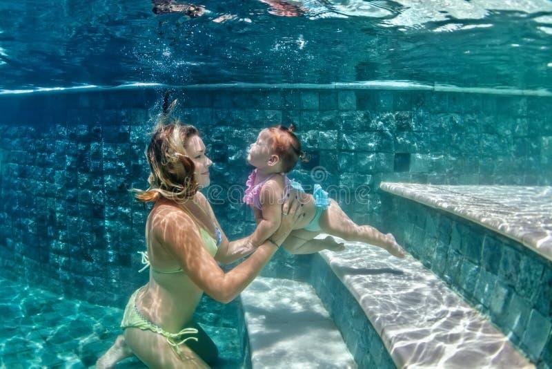 有游泳在水面下在蓝色海滩pool0的孩子的母亲 库存图片