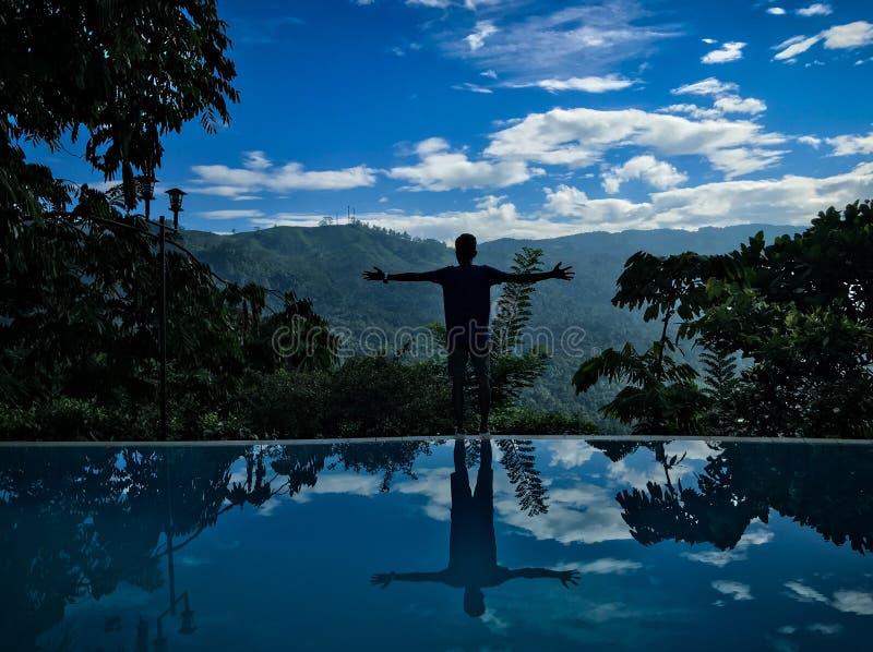 有游泳池的男孩&与蓝天的山景 库存照片