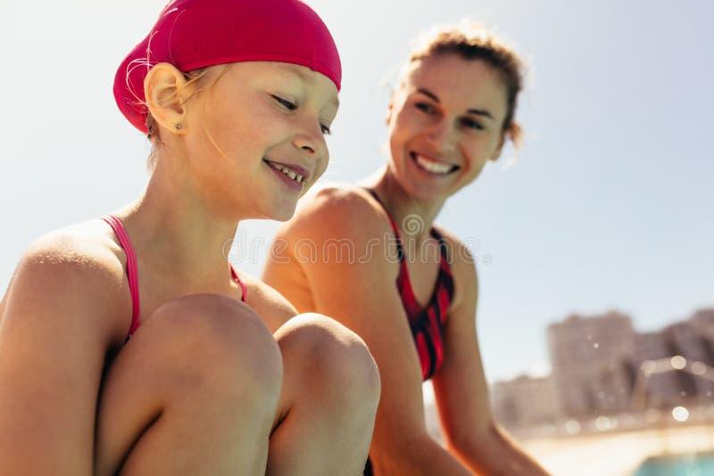 有游泳的教练的微笑的孩子 免版税库存图片