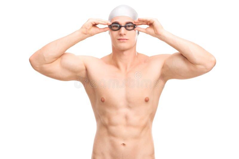 有游泳盖帽和风镜的年轻男性游泳者 库存照片