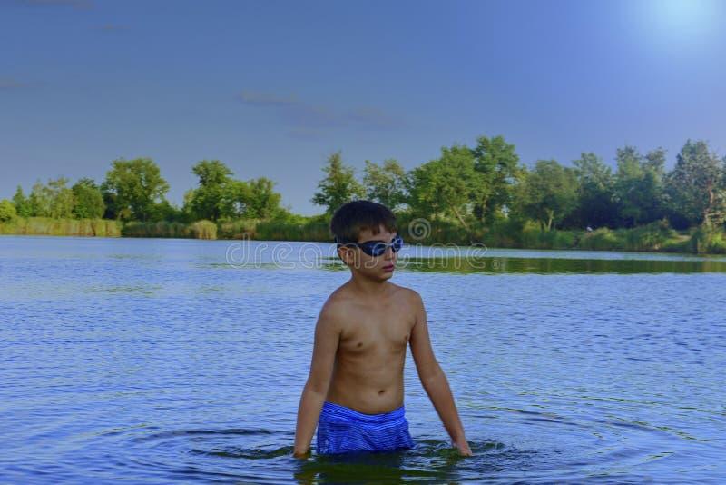 有游泳风镜的逗人喜爱的小男孩在湖站立在夏日 夏天和愉快的童年概念 复制 图库摄影