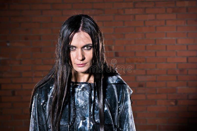 有湿头发的恼怒的妇女在雨以后 库存图片