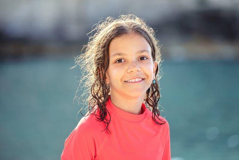 有湿头发的美丽的女孩微笑和看照相机的海滩在日落期间,愉快的孩子室外画象  免版税库存照片