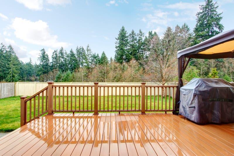 有湿甲板、格栅和篱芭的后院。 库存照片