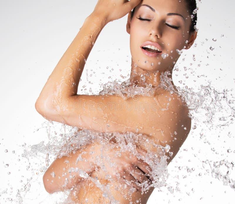 有湿身体的美丽的赤裸妇女和飞溅水 免版税库存照片