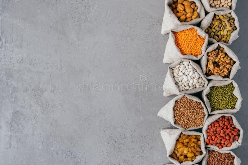 有滋补保健品的大袋在站立在行的小大袋被隔绝在与空白的拷贝空间的灰色纹理背景 免版税库存图片
