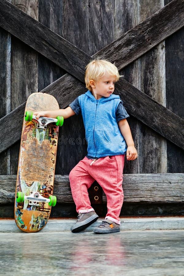 有滑板的滑稽的矮小的溜冰者在教训前 图库摄影