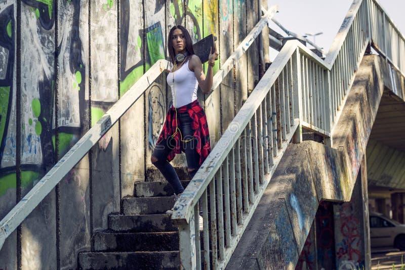 有滑板的青少年的女孩 户外,都市生活方式 图库摄影