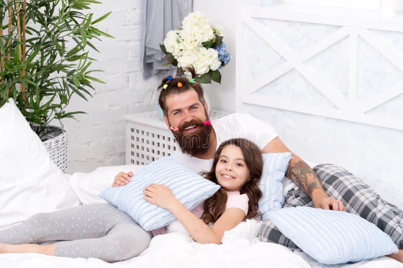 有滑稽的发型马尾辫和女儿的父亲有胡子的人睡衣的 有乐趣睡衣派对 大会串 免版税库存图片