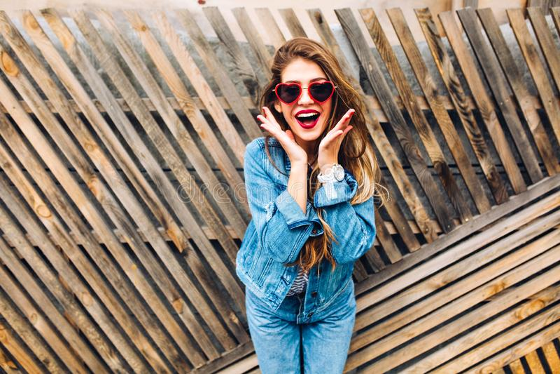 有滑稽的快乐的面孔表示的俏丽的女孩听说她的在抽奖的胜利 减速火箭的惊奇的可爱的年轻女人 免版税库存照片