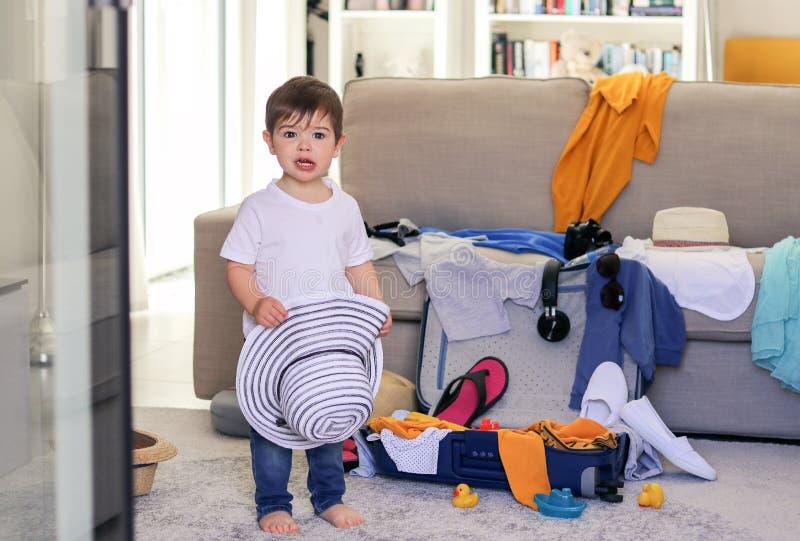有滑稽的惊奇的面孔表示藏品帽子的逗人喜爱的矮小的男婴在帮助的手上包装手提箱包装的衣裳和玩具f 免版税库存图片