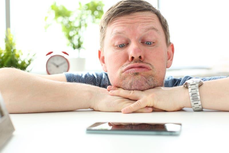 有滑稽的表情的人凝视手机的 免版税库存图片