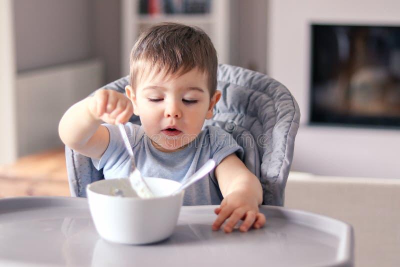 有滑稽的被抹上的面孔的逗人喜爱的矮小的男婴集中食物吃与从白色碗的叉子在他前面的桌上sittin的 库存照片